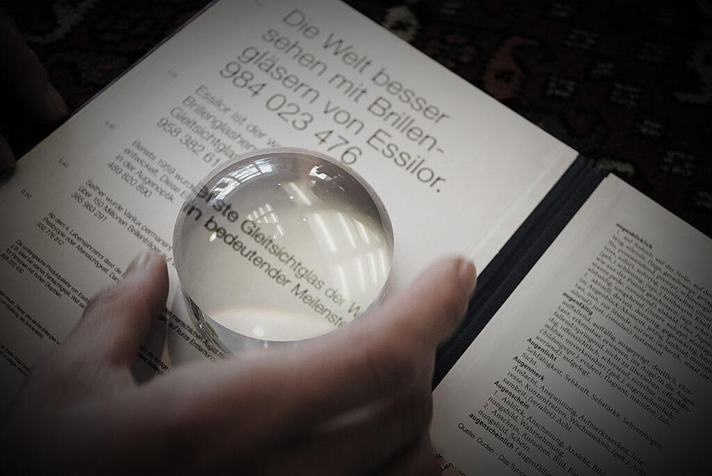 imagebild-kontaktlinsen-glas-liegt-auf-leseprobe-und-vergroessert-schrift