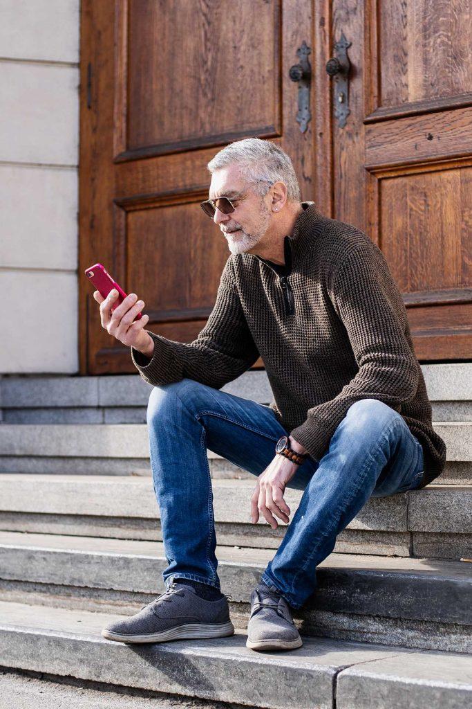 Kunde mit Sonnenbrille und Handy vor den Stufen der Grazer Oper
